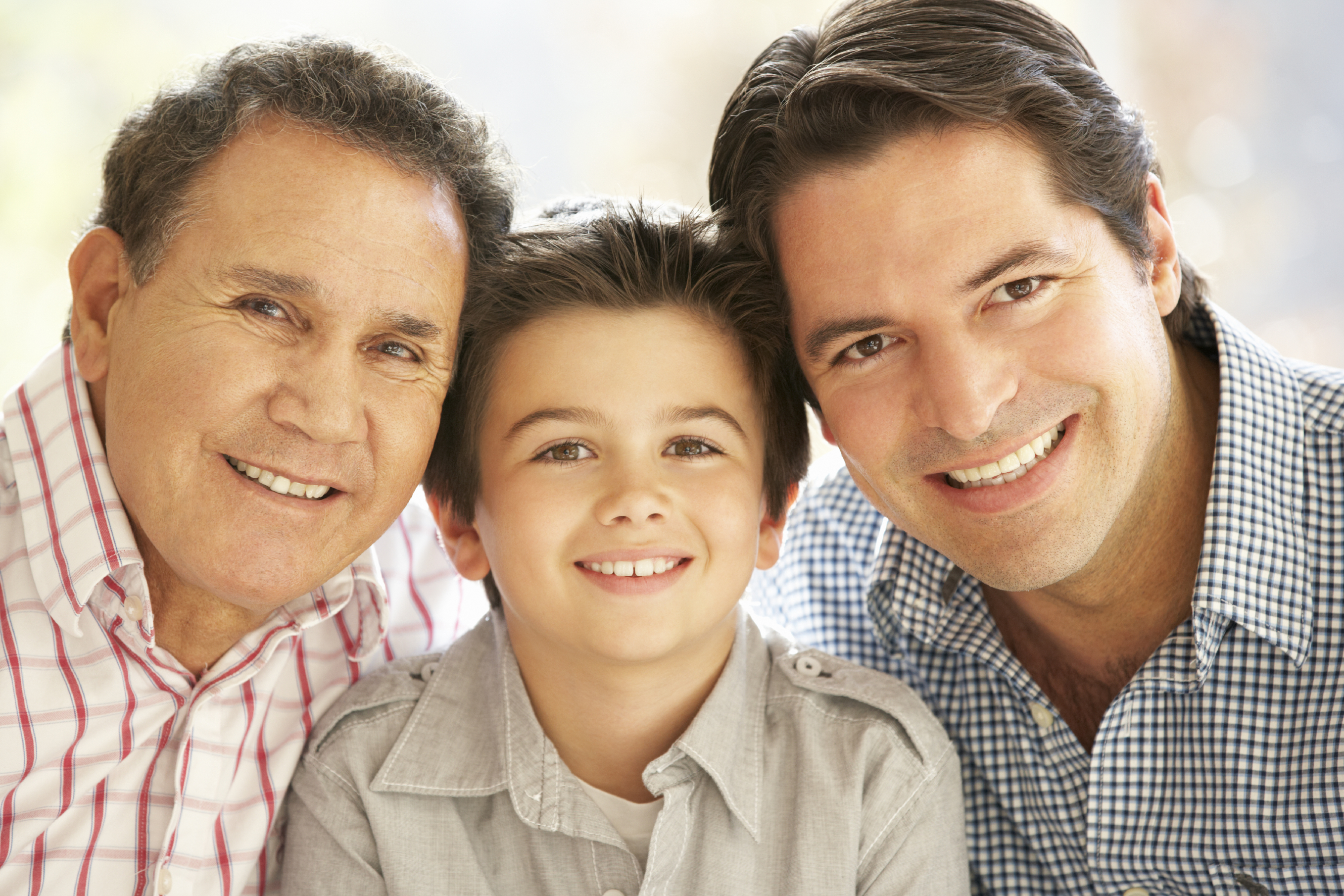 Portrait Of Hispanic Grandfather, Adult Father And Son Relaxing